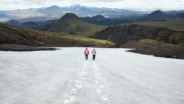 Couple descending snow field