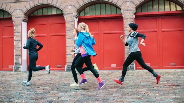 Full length of sporty women jogging on sidewalk in city