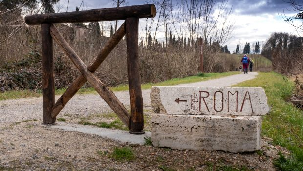 Stone signs towards Rome on the Via Francigena, departure from Siena to Ponte d'Arbia. Plowed fields and cereal hills with solitary trees, conclusion of the route along the Via Cassia - Tuscany, Italy (Stone signs towards Rome on the Via Francigena, d