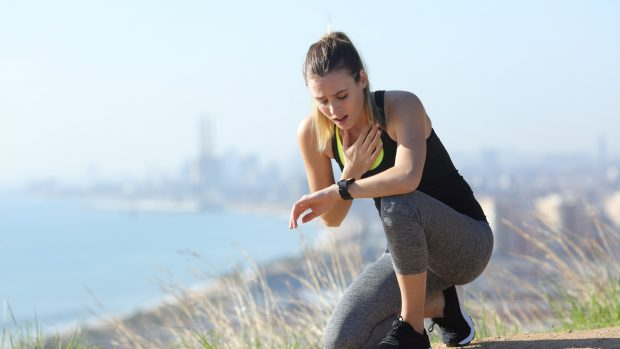Tired stressed runner controlling pulsations checking smartwatch after exercise in city outskirts